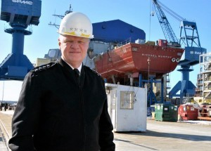 CNO Adm. Gary Roughead poses for a photo with the keel of the Michael Murphy, which will be christened later this year, during a visit to Bath Iron Works.