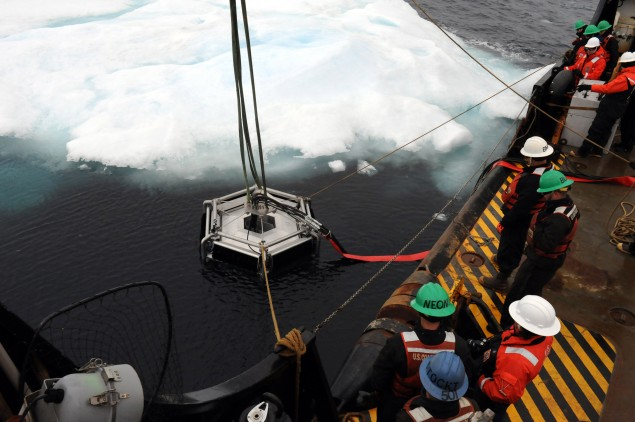 "Coast Guard personnel aboard the Coast Guard Cutter Sycamore set a DESMI ""Polar Bear"" skimmer into the Arctic Ocean."