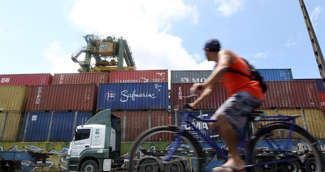 A dock worker rides his bicycle in front of containers at the port of Santos February 22, 2013. REUTERS/Paulo Whitaker