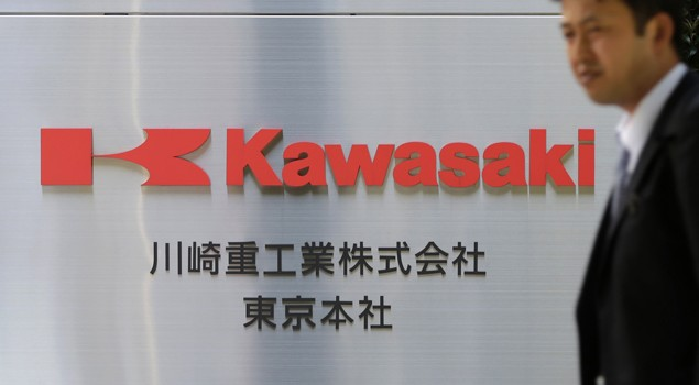 A man walks past a signboard of Kawasaki Heavy Industries, Ltd. at the company's Tokyo Head Office in Tokyo April 22, 2013. Image (c) REUTERS/Toru Hanai