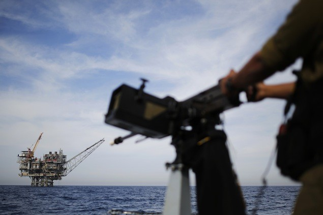 An Israeli gas platform is seen in the back as a sailor in the Israeli navy stands aboard a patrol boat in the Mediterranean sea some 15 miles (24 km) west of the port city of Ashdod February 25, 2013. REUTERS/Amir Cohen