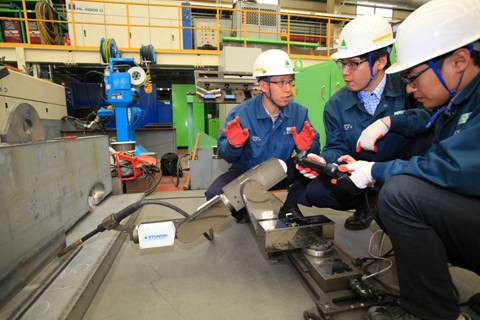 Operators get a feel for HHI's new miniature welding robots. Photo: HHI